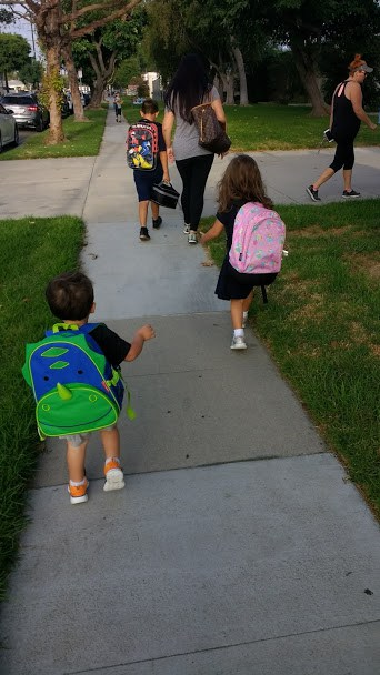 Two children walking to school with backpacks on.