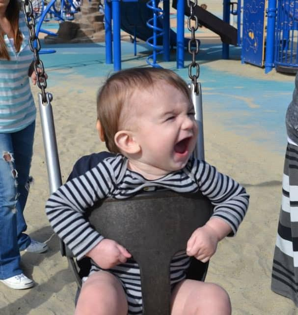 Baby sitting in a swing at a park