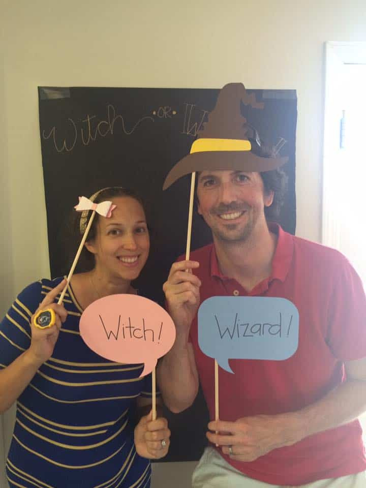 """Two adults with """"Witch"""" and """"Wizard"""" pink and blue signs."""