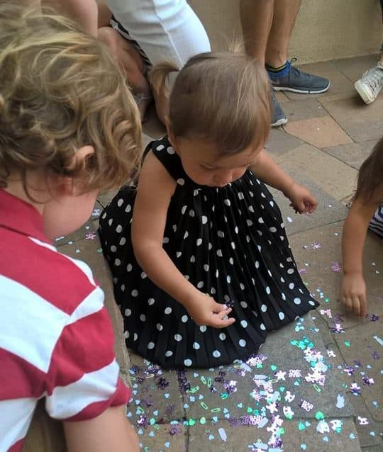 Toddlers playing with confetti at a gender reveal party
