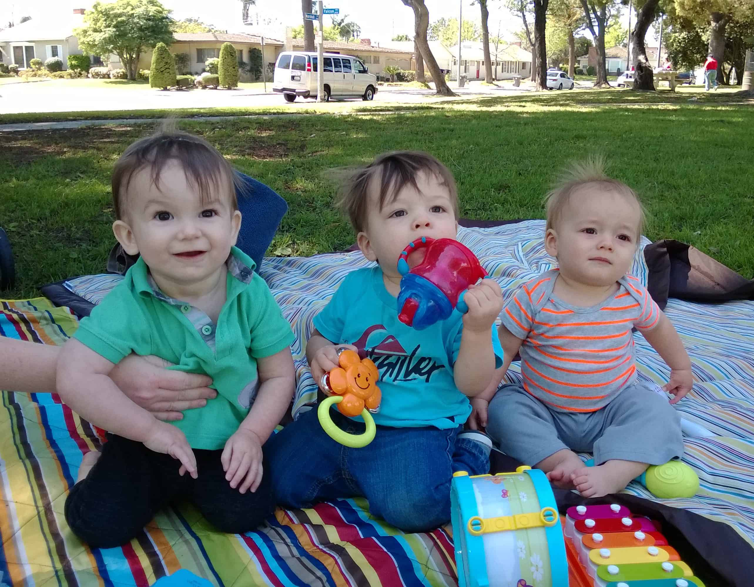 Three young babies sitting on a mat for socialization time.