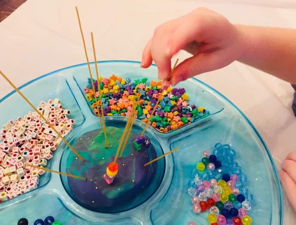 threading beads onto spaghetti in playdough