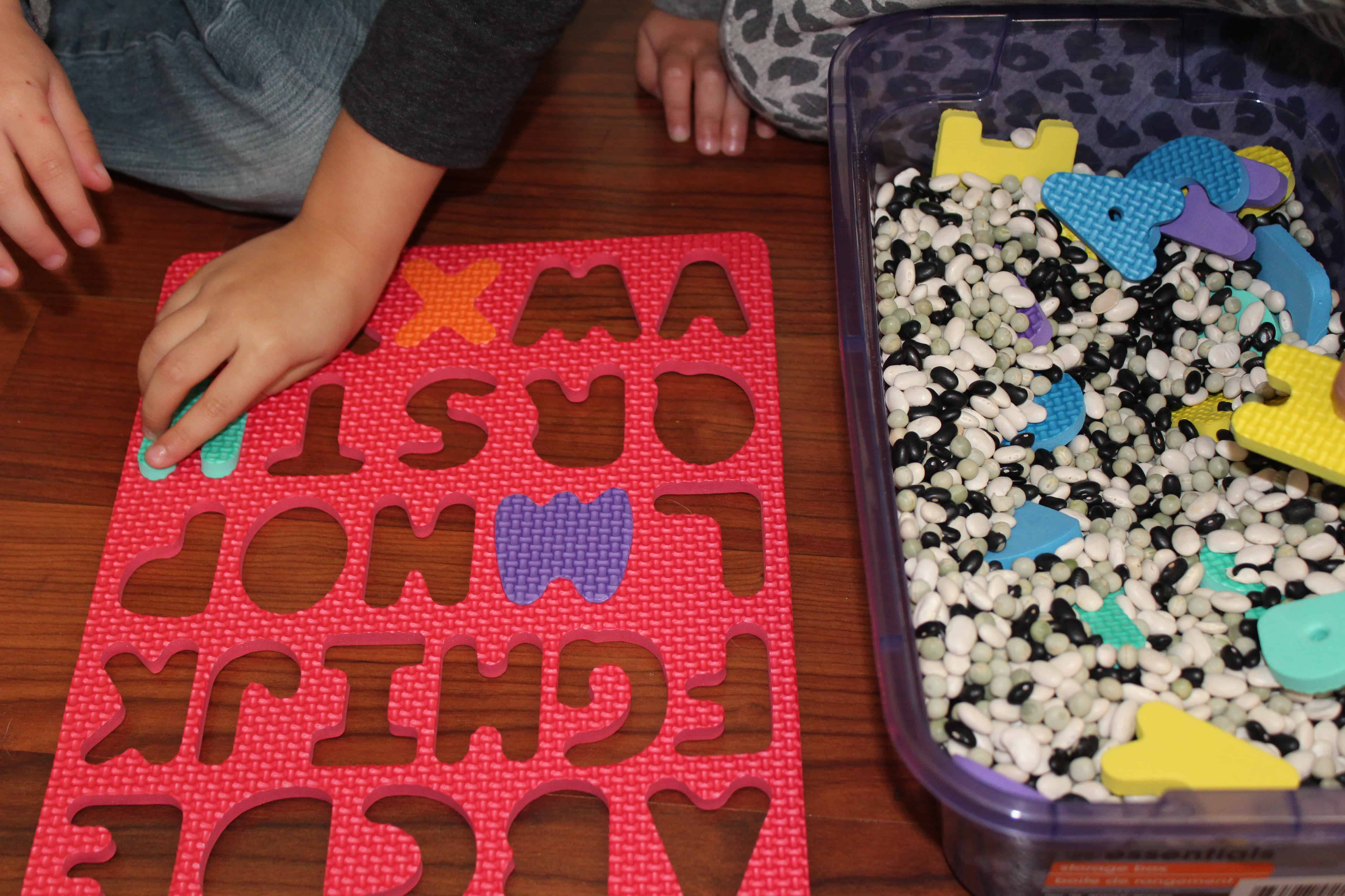Children playing with a foam letter puzzle and sensory bin