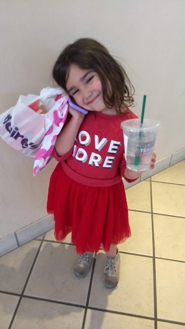 preschooler shopping, drinking from starbucks cup