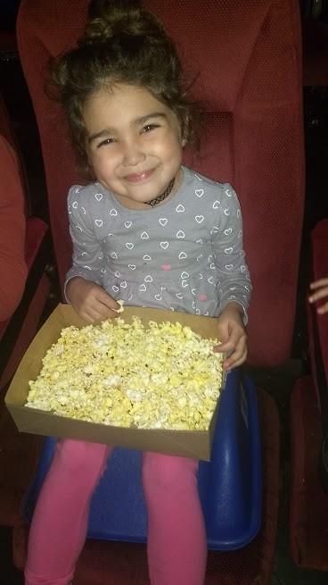 toddler eating popcorn at the movies
