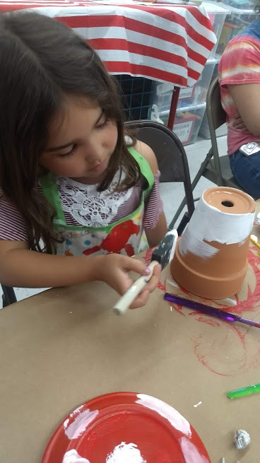 daughter painting a flower pot at michaels