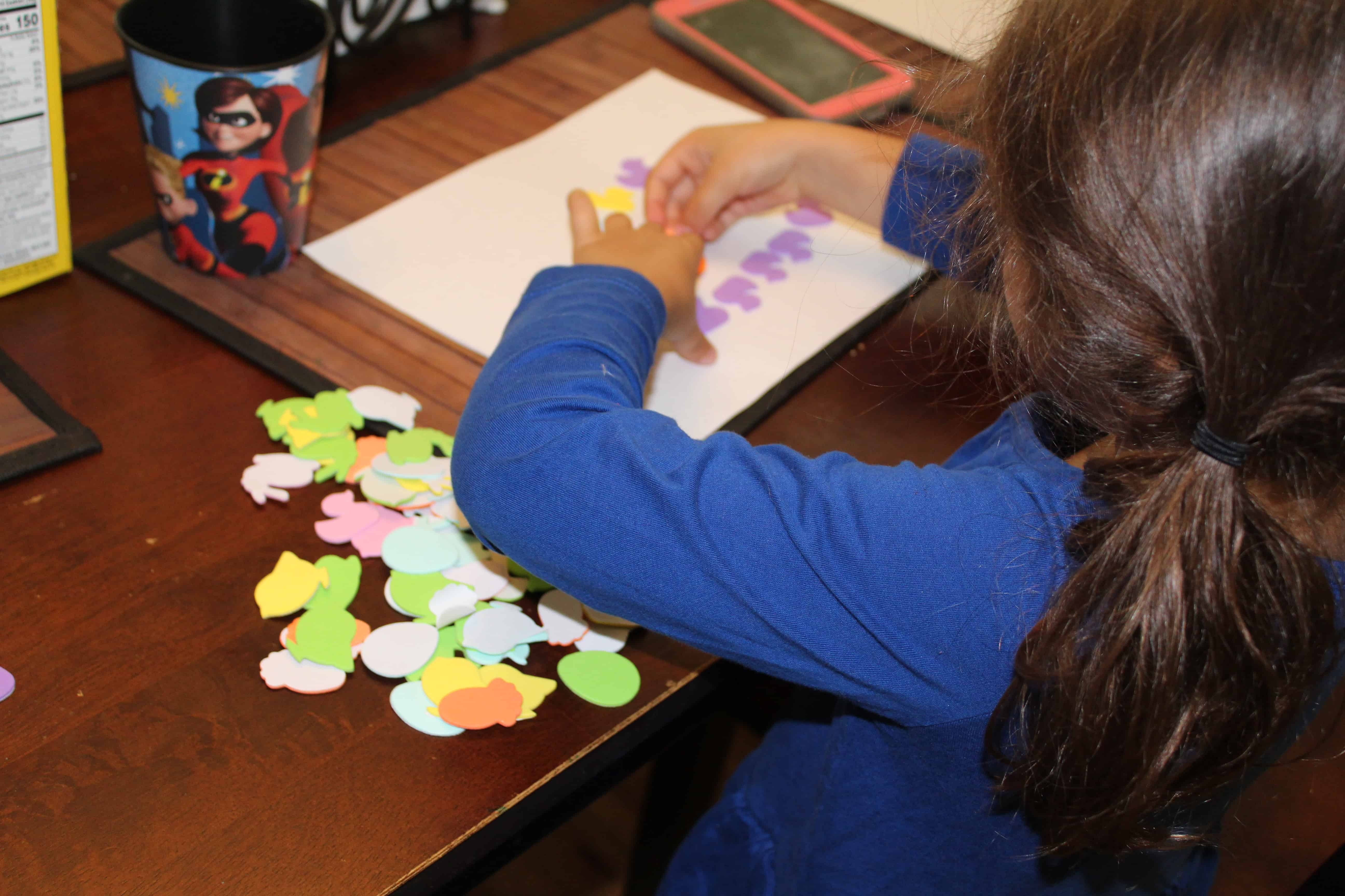Child using foam stickers on white paper.
