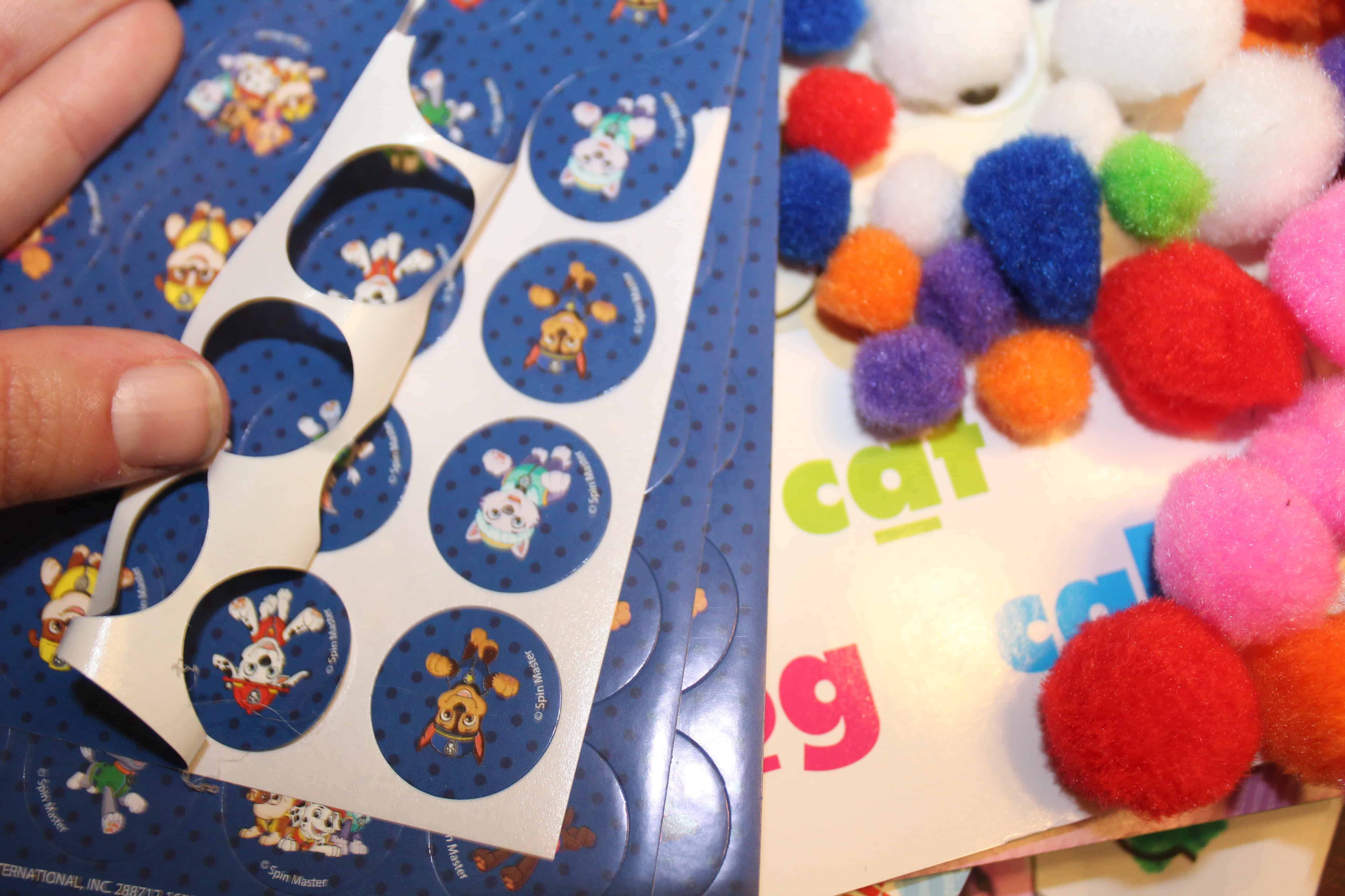 Regular stickers with boarder being removed and colored cotton balls.