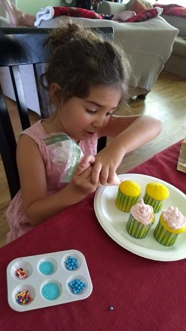 preschooler decorating cupcakes