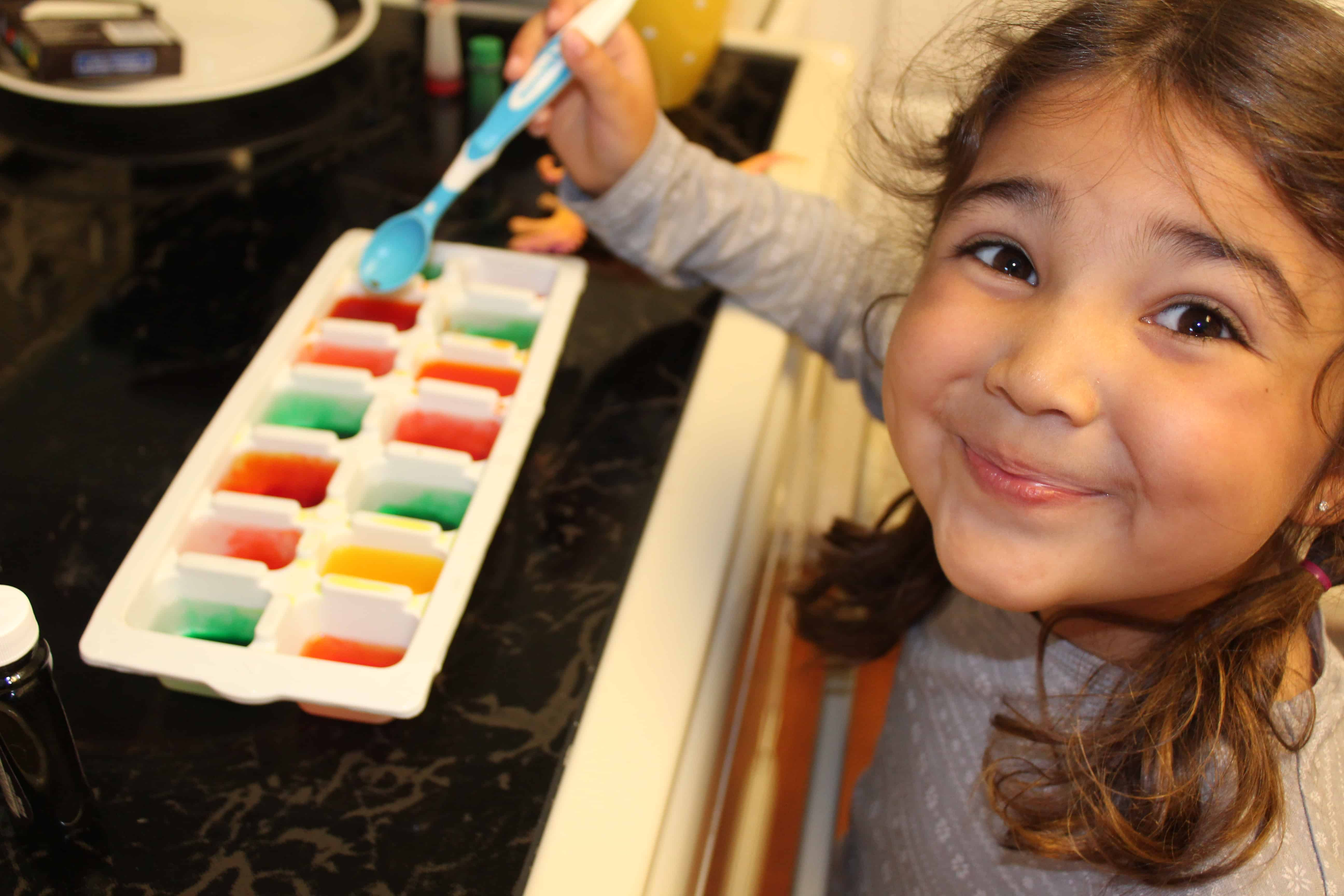 Child smiling with ice tray full of water and food coloring