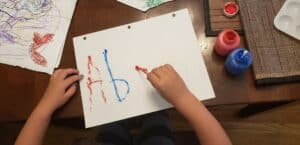 a child tracing their name with a qtip dipped in paint