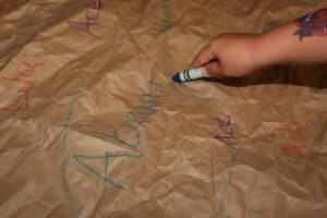 child circling their name, written on a piece of butcher paper