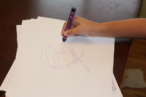 child scribbling on a paper