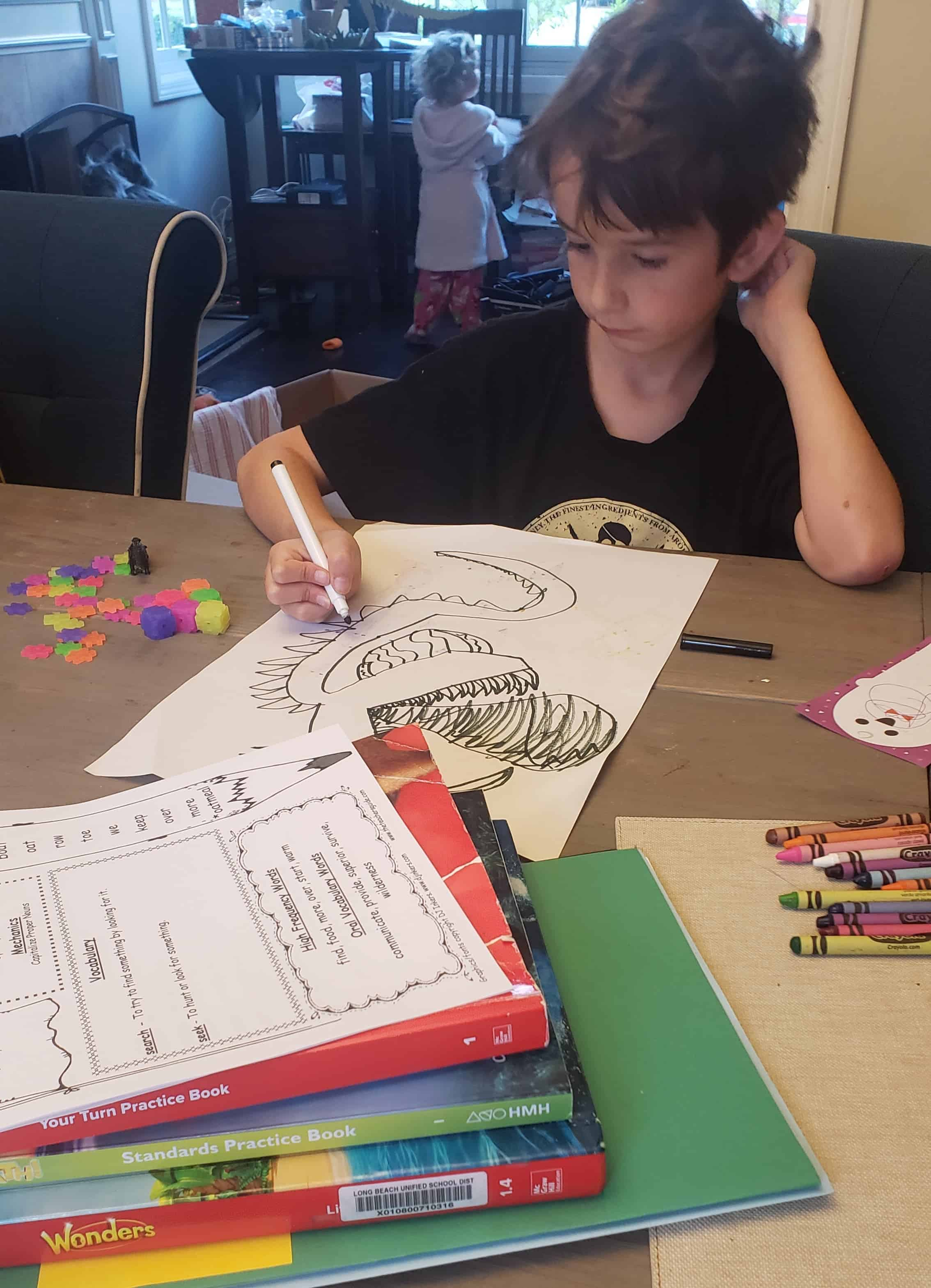 Child drawing artwork at the table.