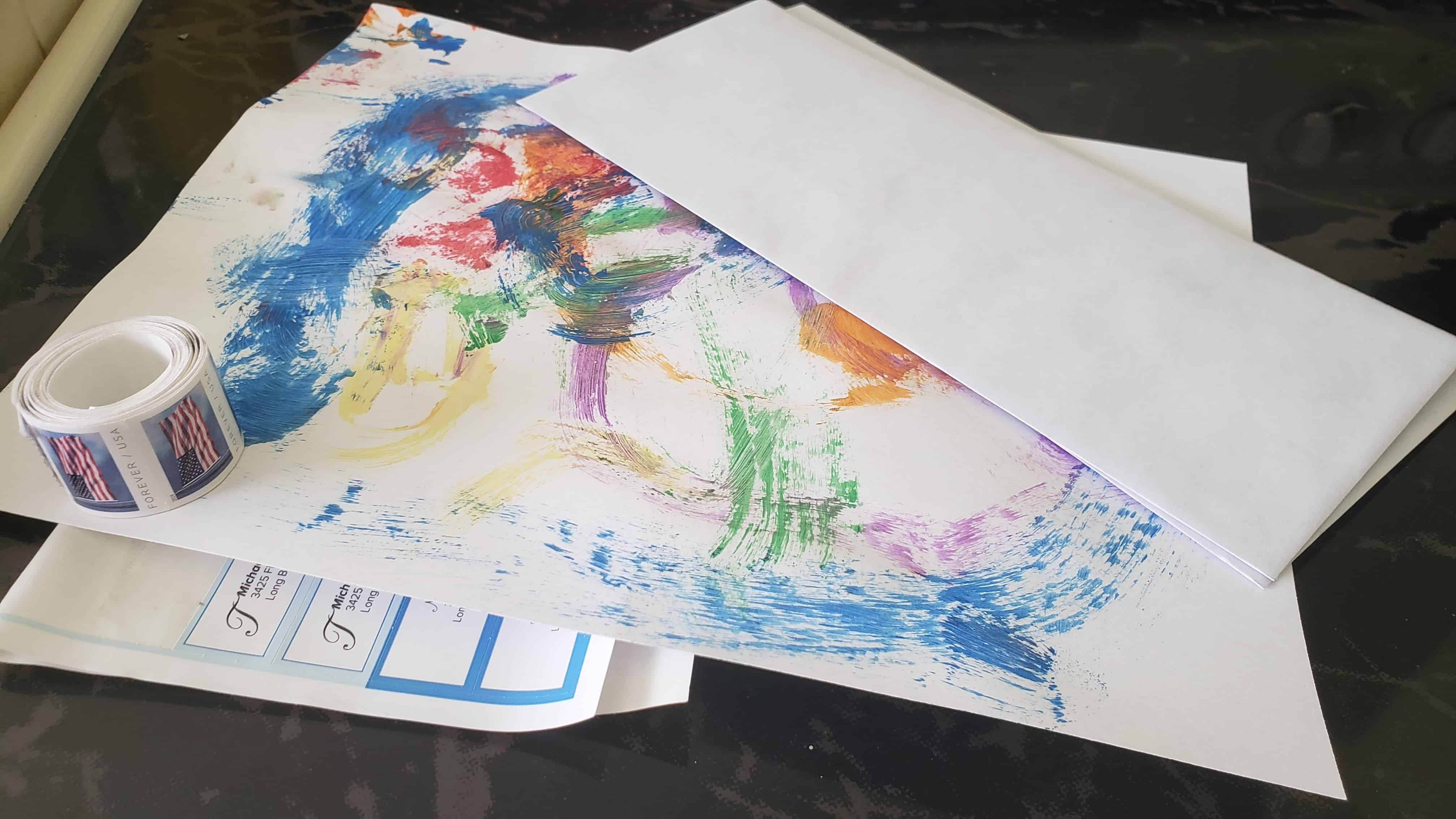 A roll of stamps, an envelope and a sheet of paper with painted artwork on it.