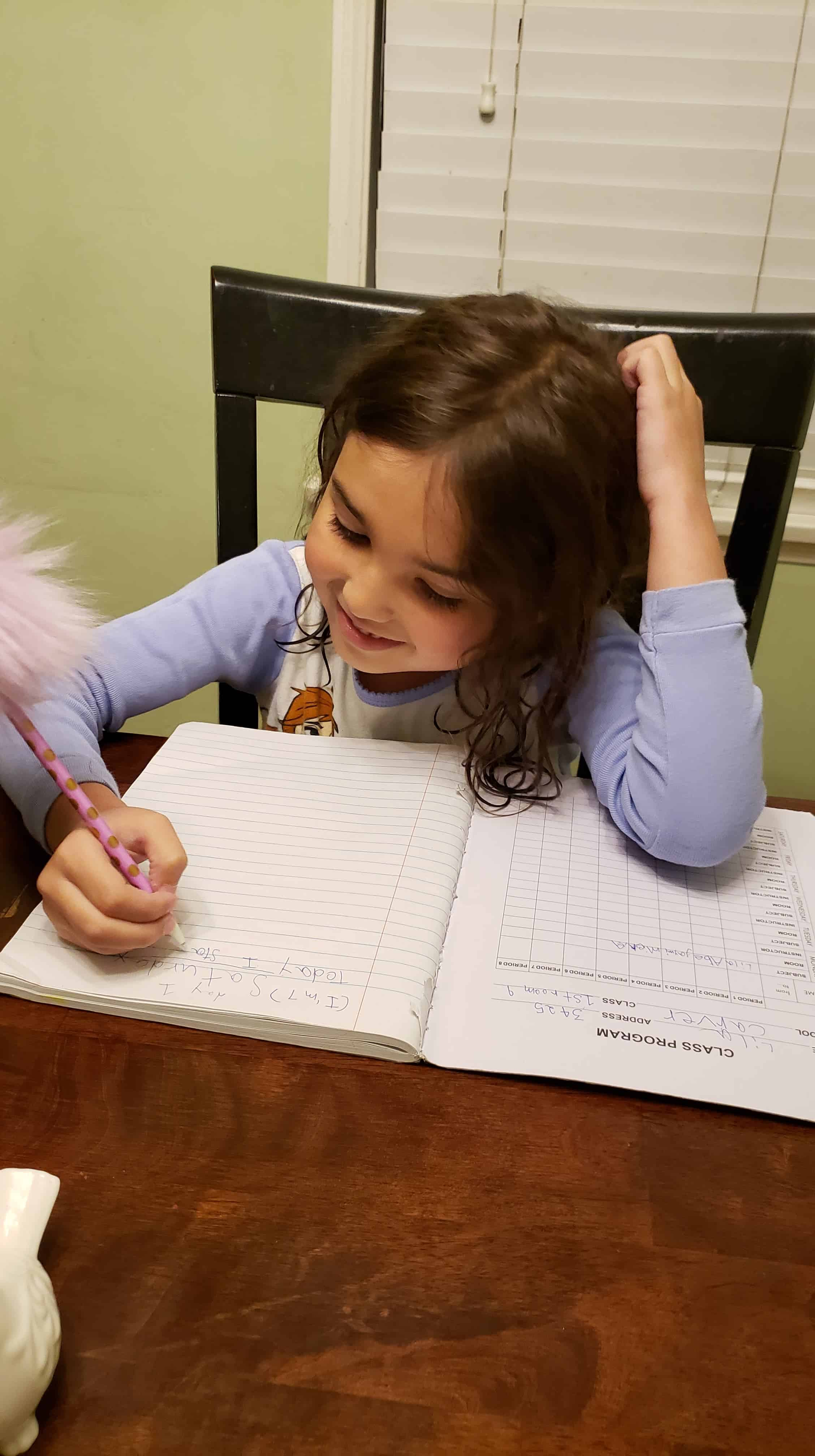 Little girl writing in a composition notebook.