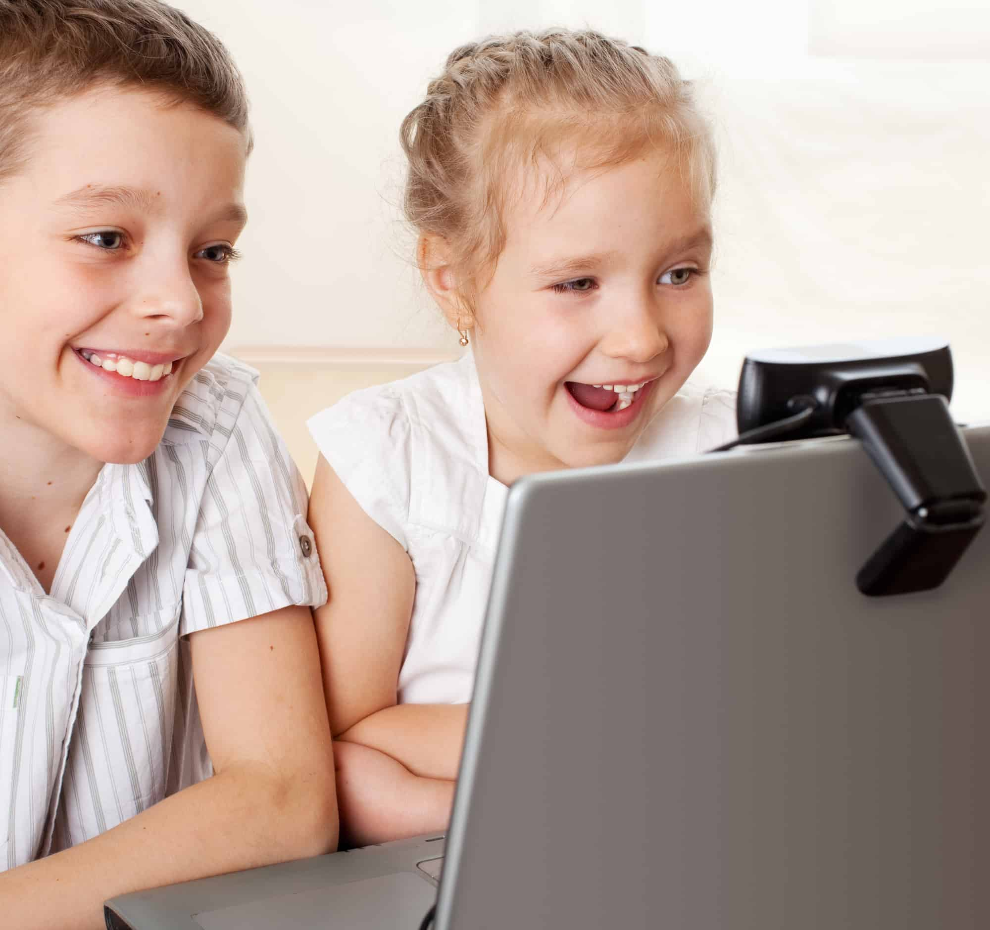 Two children smiling and laughing on the computer as they face time.