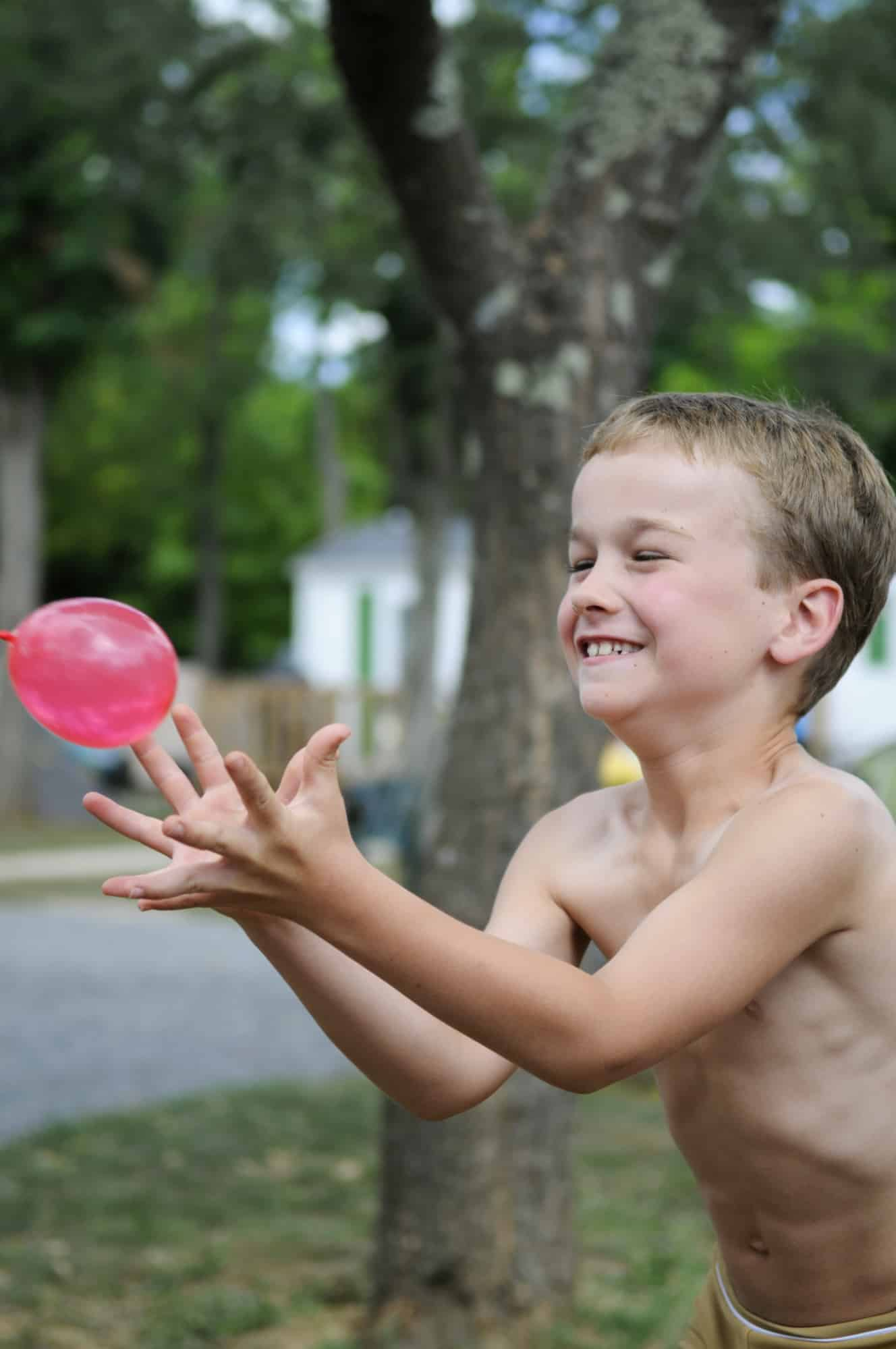 Little boy smiling while catching a water balloon.