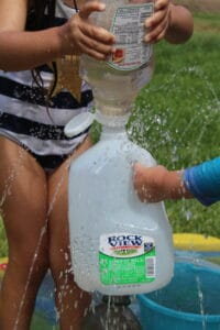 little girl using a ketchup bottle to squirt water into a milk jug
