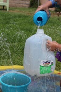 kids using milk jugs to play with water