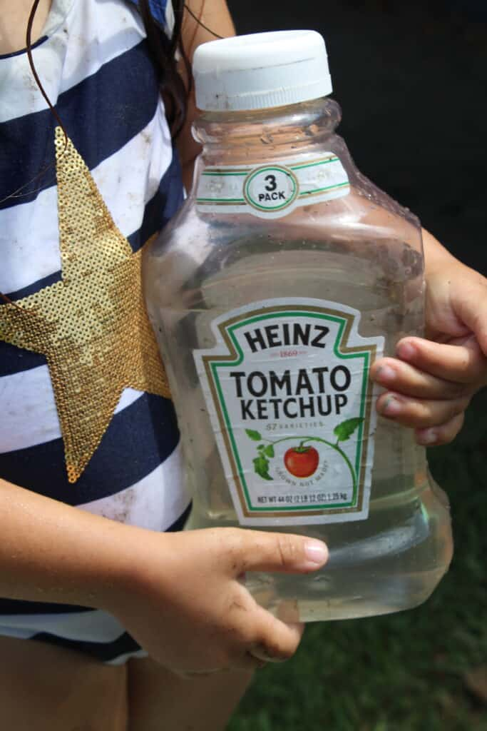 little girl holding a recycled ketchup bottle