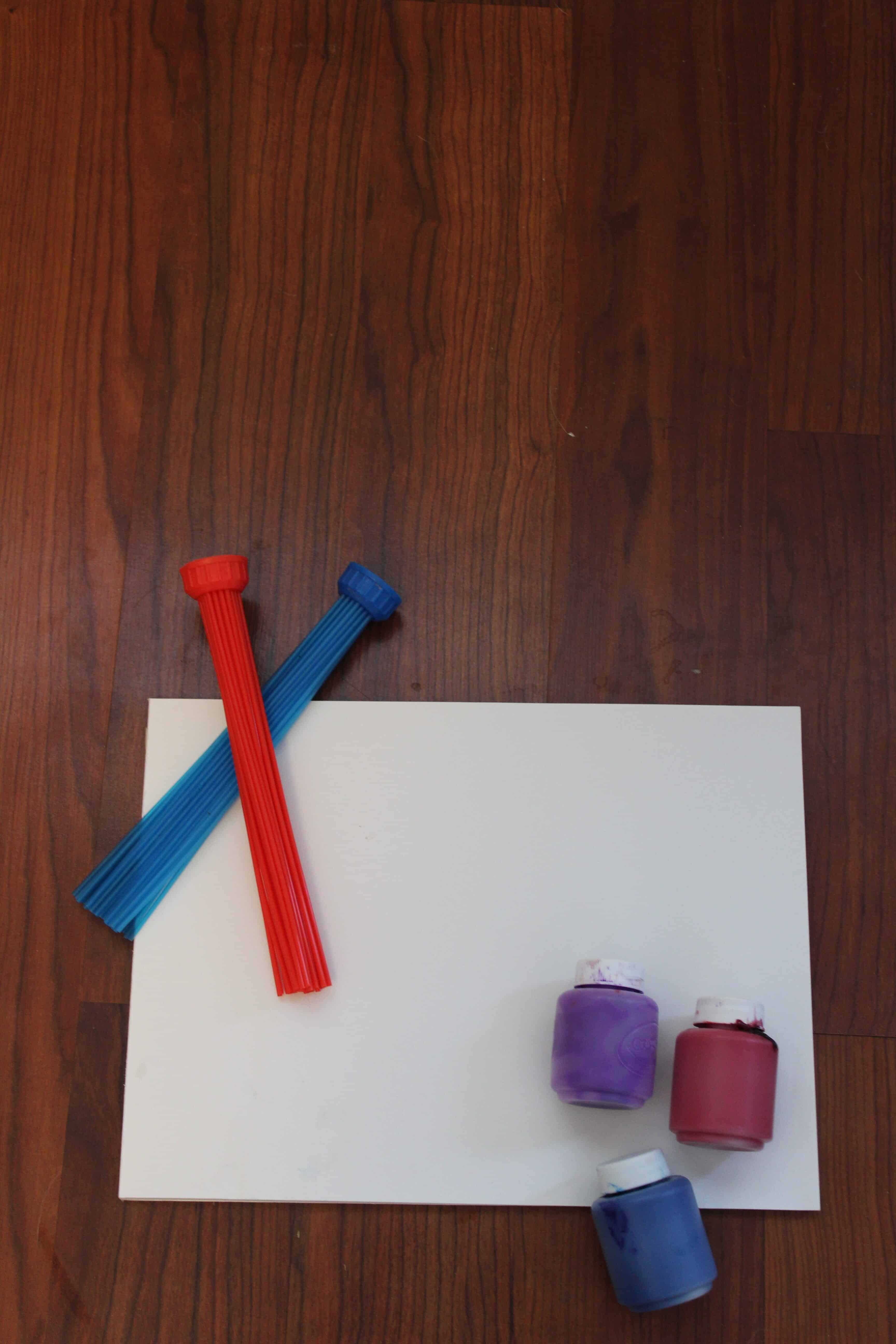 Bunch a balloons fast filler being used as a paintbrush resting against a white sheet of paper. Blue, purple and red paint in bottle.