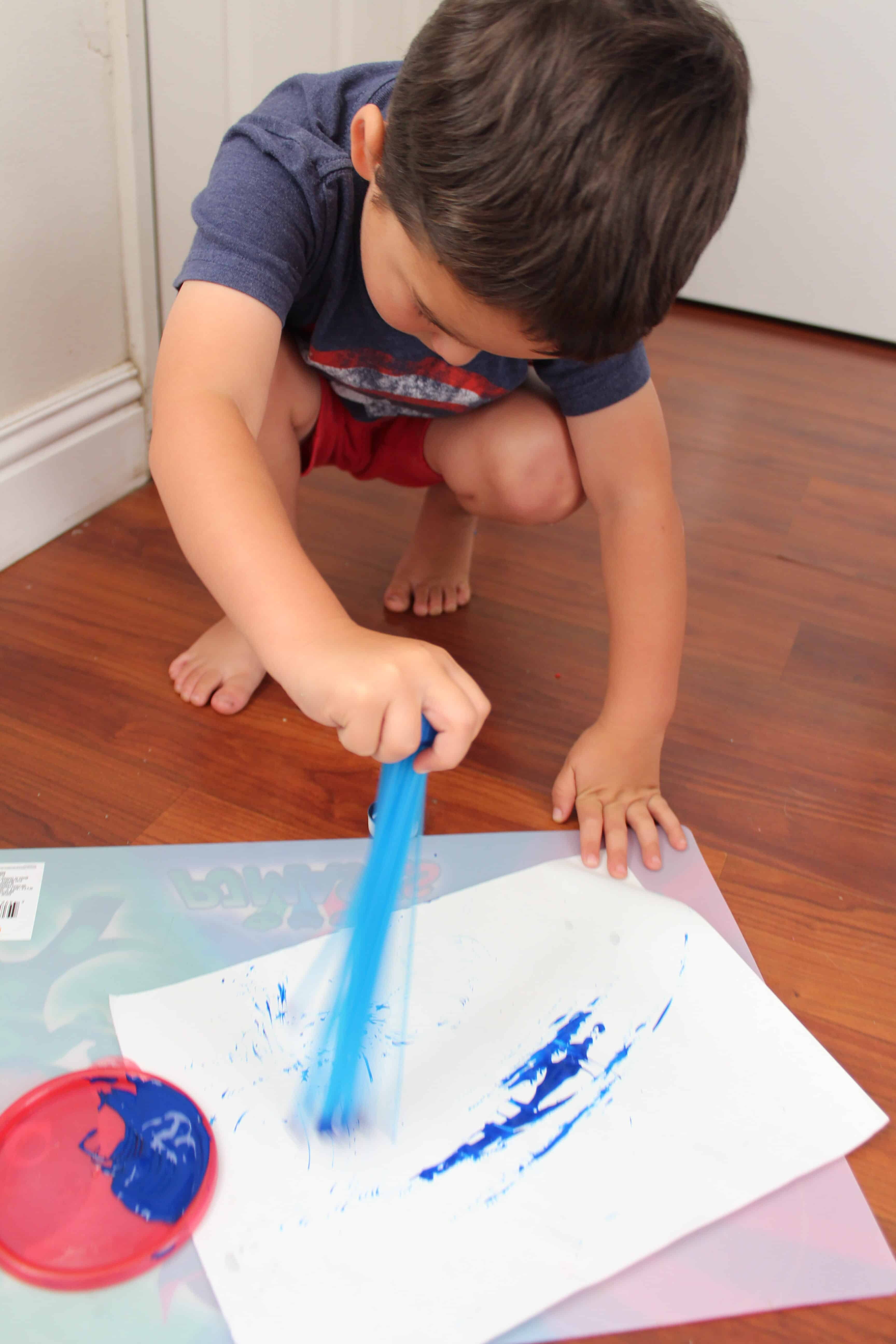 Toddler crouched using the bunch a balloons at the paint brush.