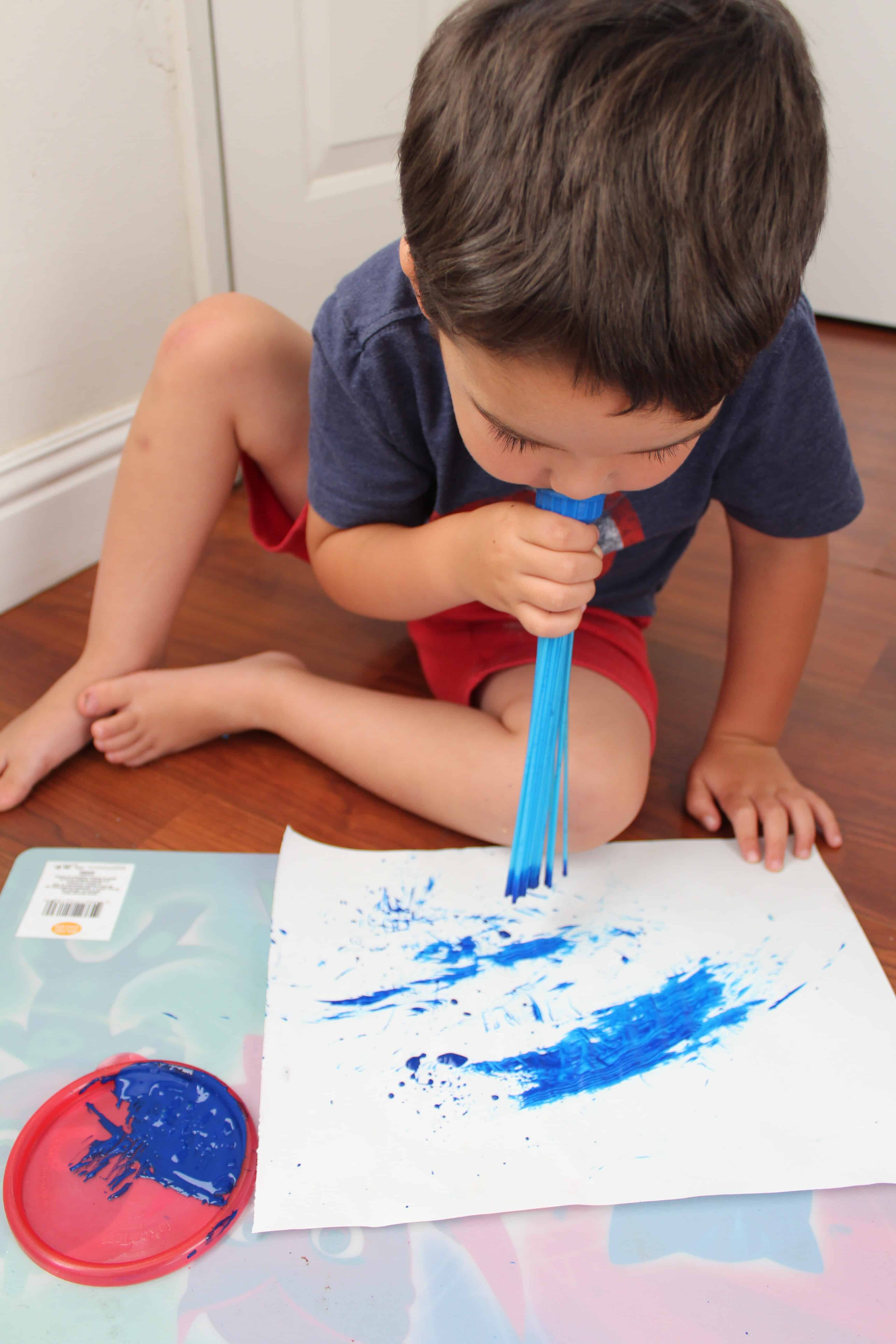 Toddler blowing on the bunch a balloons maker end cap to push pain onto the paper.