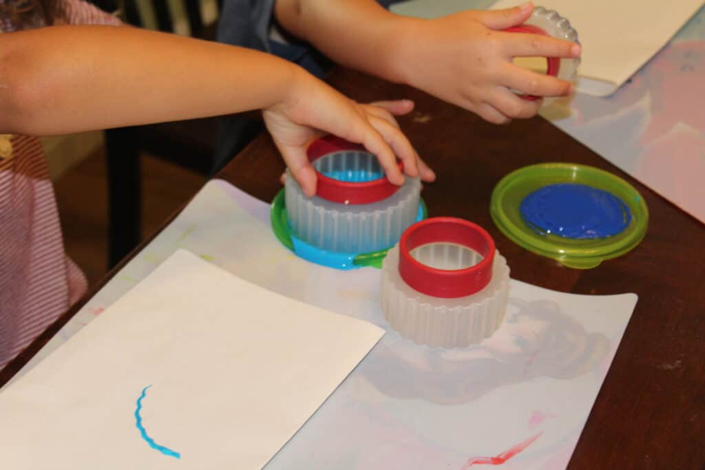 kids dipping cookie cutters in paint to use like stamps