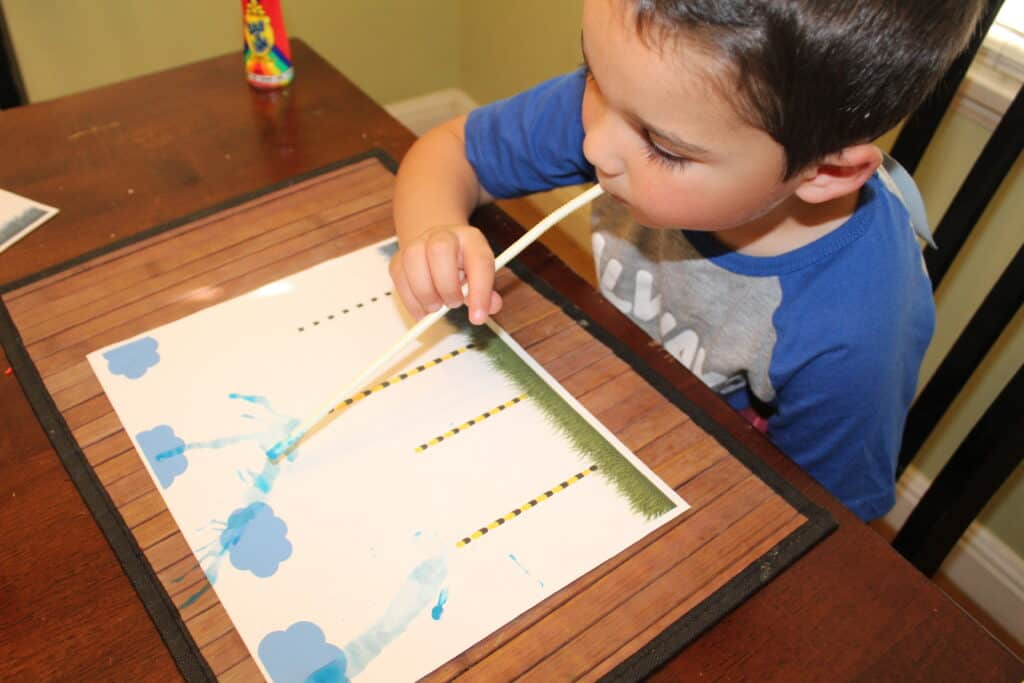 toddler using a straw to make paint truffula trees