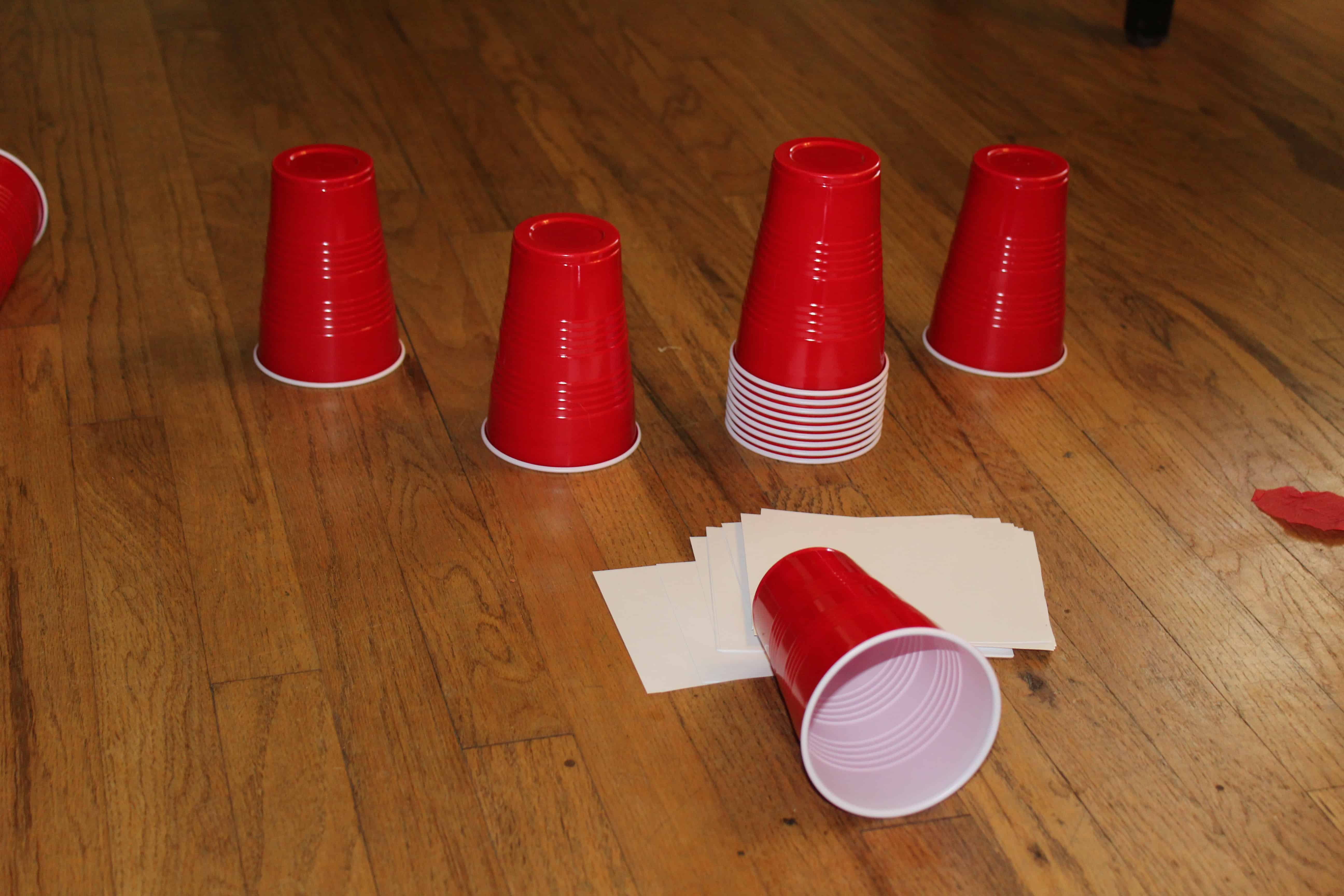 red solo cups and small pieces of paper sitting on the floor