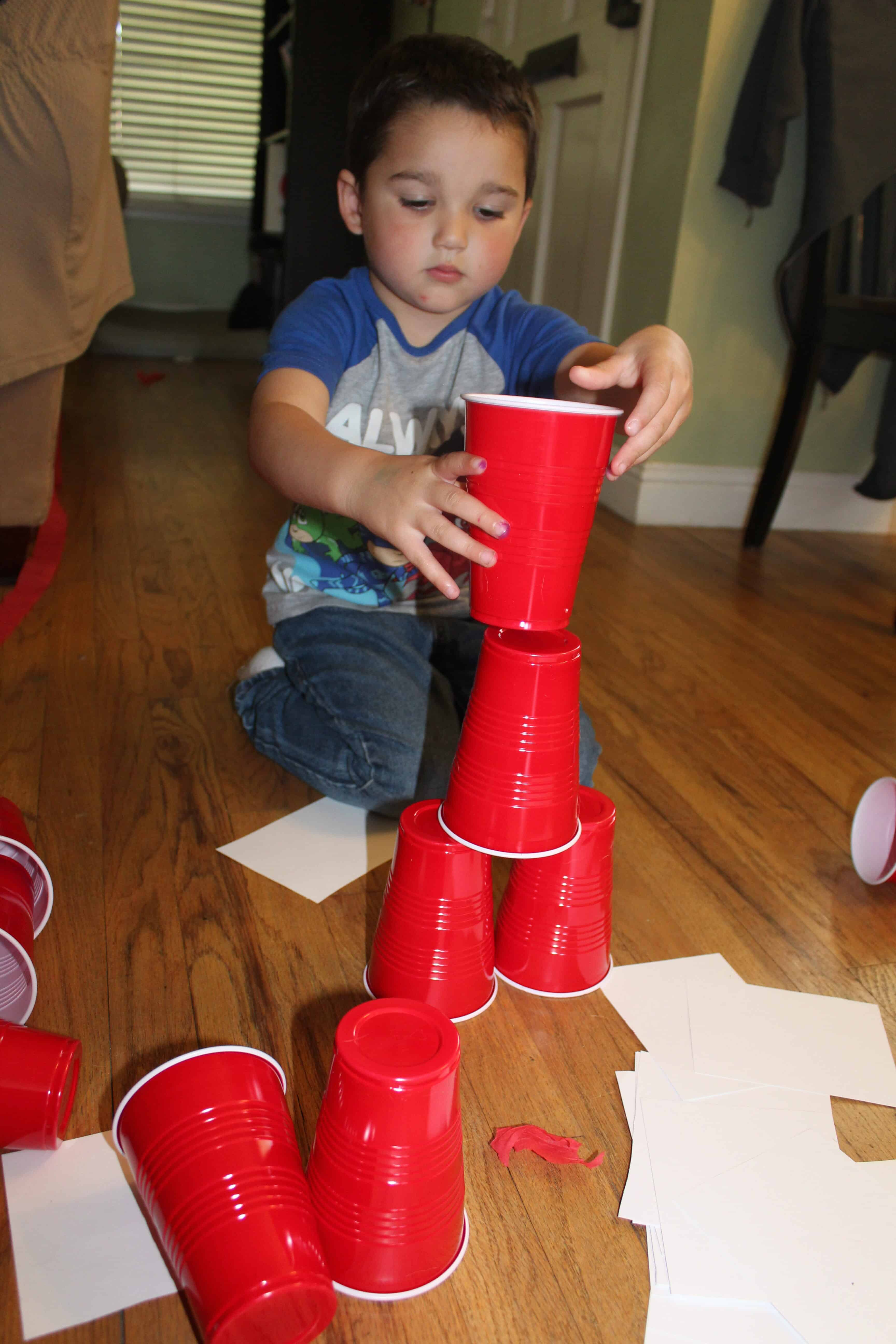 toddler building a tower of red solo cups