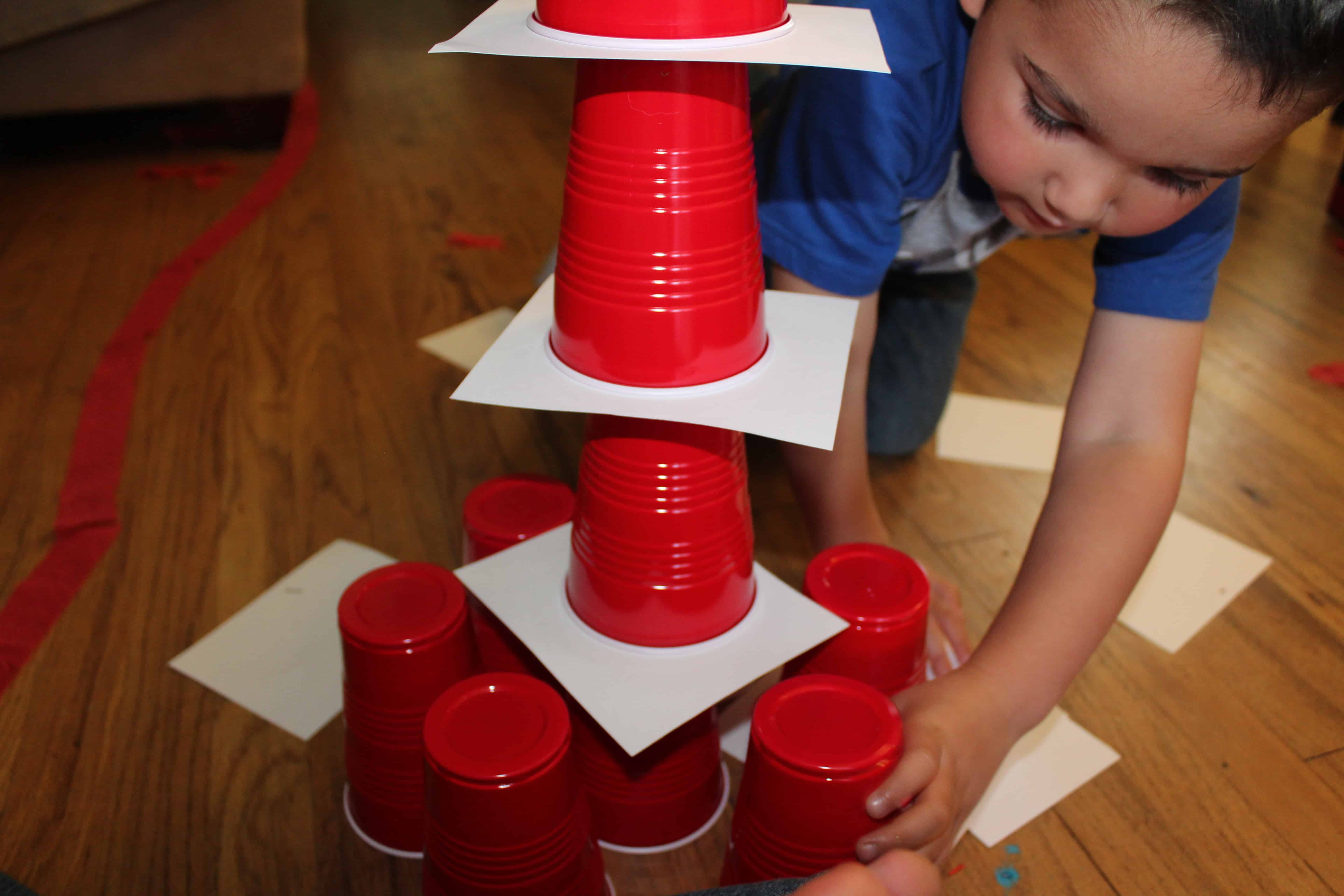 preschooler building a tower with red solo cups and white paper