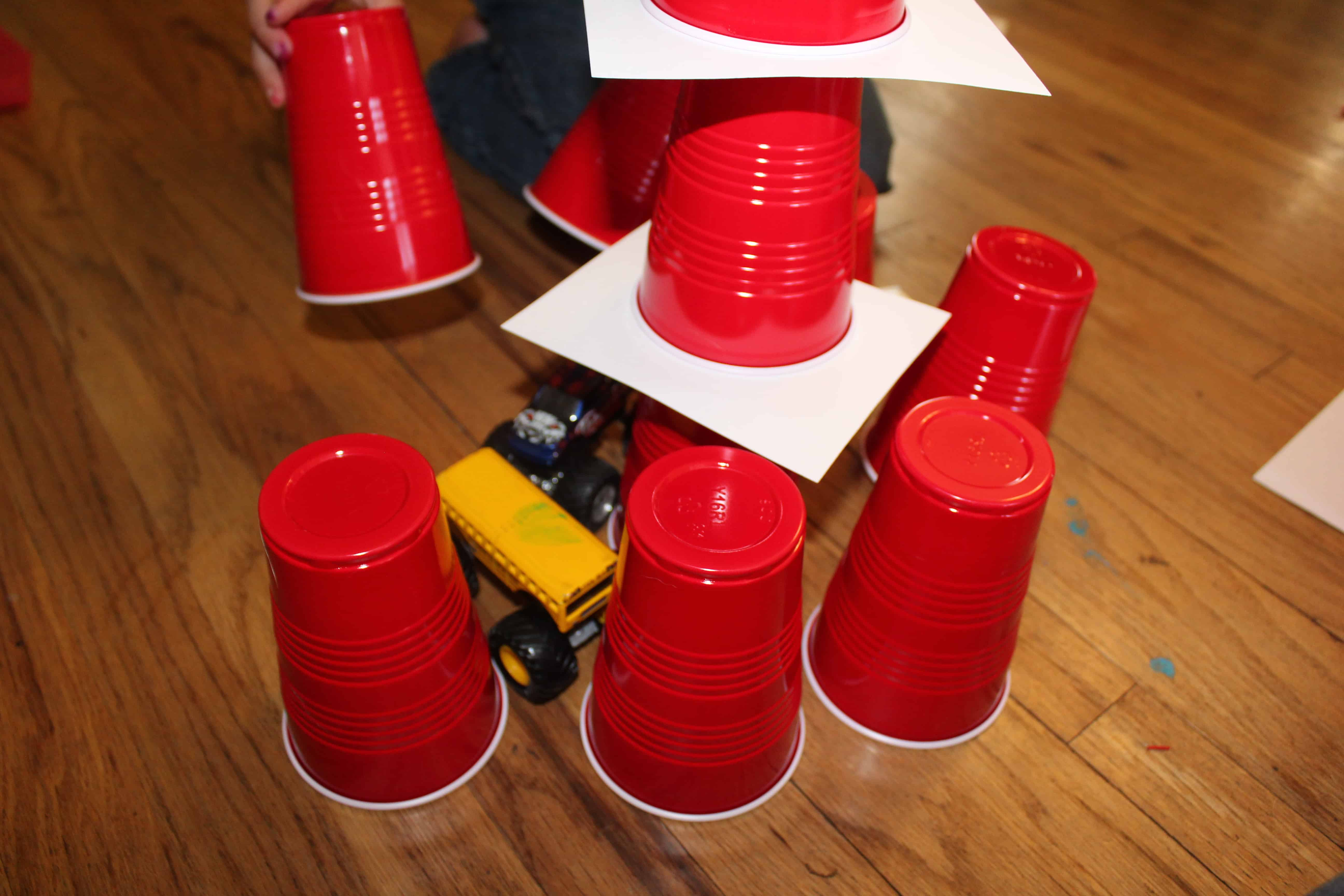 preschooler building with solo cups and trucks