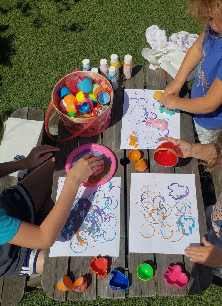 Small children using plastic easter eggs as paint stamps to create Easter Egg art