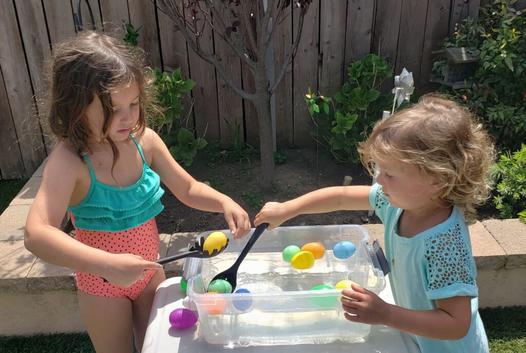 Two little girls using spoons to scoop plastic Easter eggs out of a plastic bin full of water