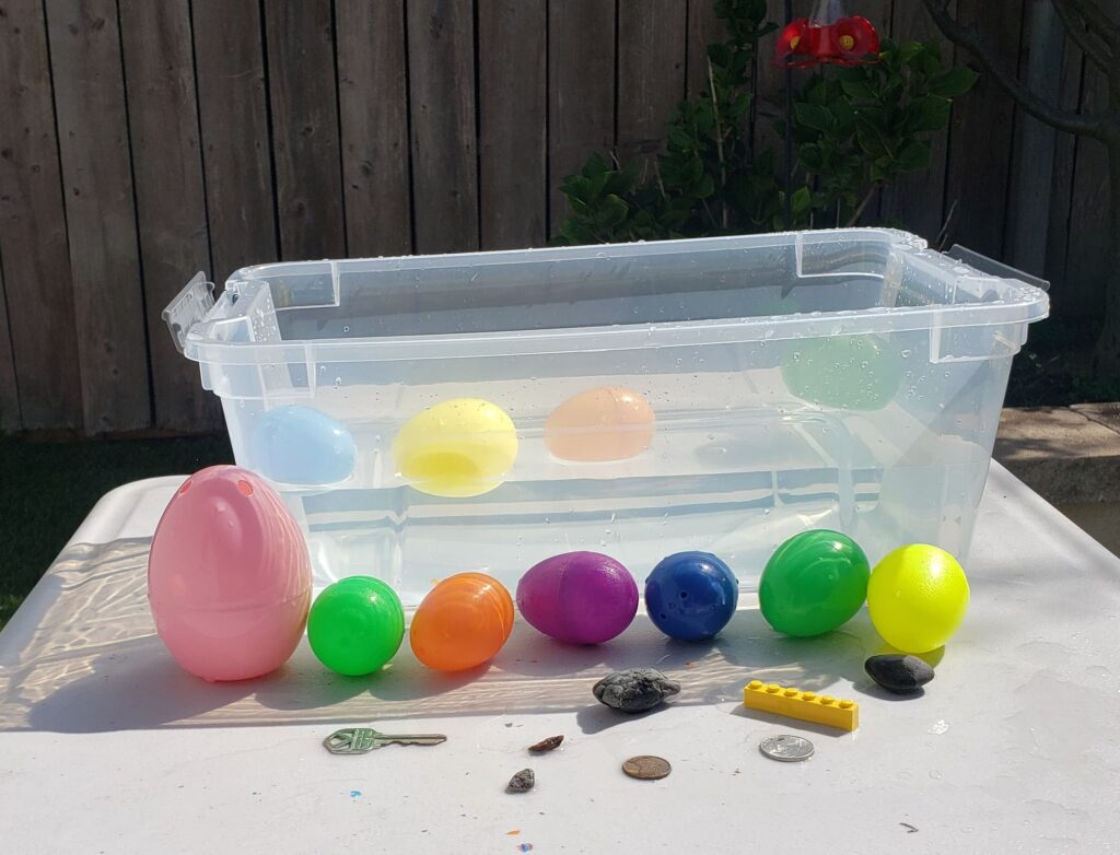 Plastic tub filled with water, plastic easter eggs and household items to use to play Sink or Float