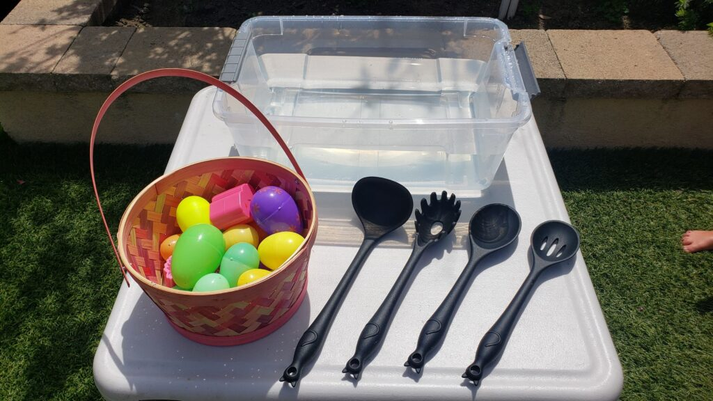 Plastic tub filled with water, plastic Easter eggs and four different styles of kitchen spoons