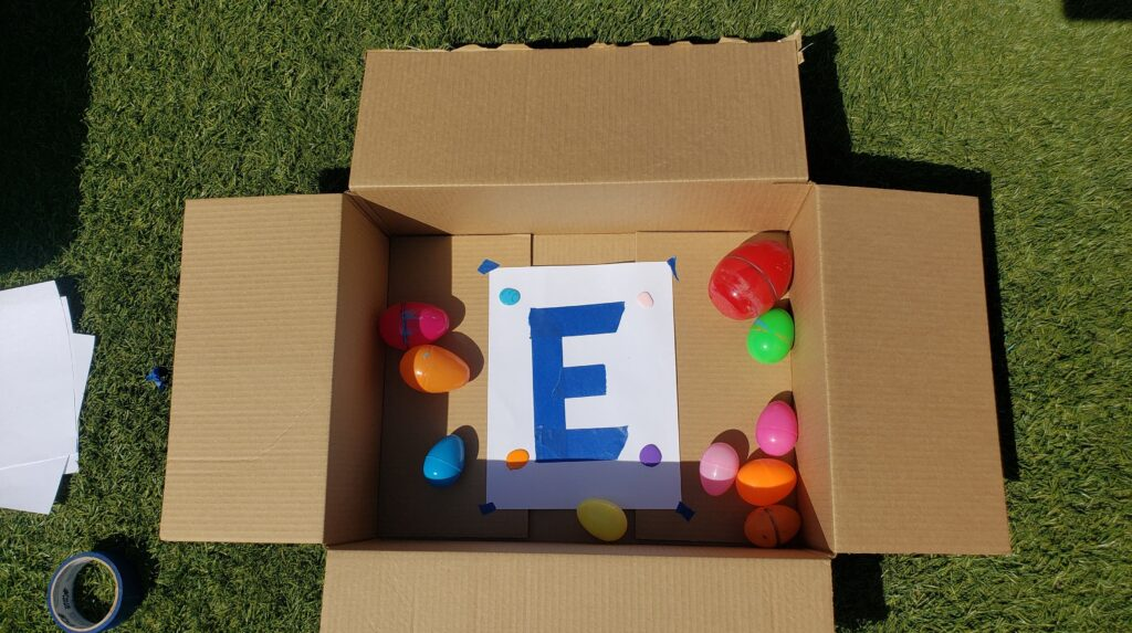 Cardboard box with a paper inside. Plastic Easter eggs and paint are inside as well to create egg roll art!