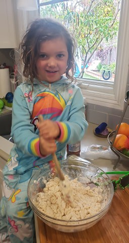 Child Mixing dough made of water, flour, and salt