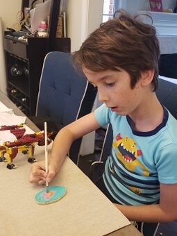 Child painting a dough ornament with pink petals.