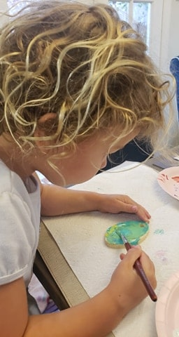 Toddler painting an egg ornament with bright colors.