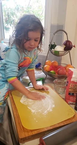 Little girl dusting a cutting board with flour to work the dough on.