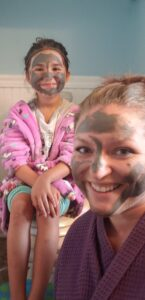 a mom and a daughter with mud masks on their faces