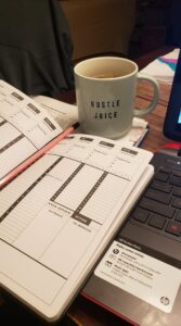 "a planner and a cup of tea in a mug that says ""hustle juice"""