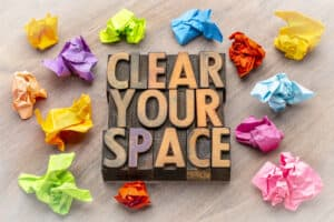 "an image of type-blocks spelling ""clear your space"" with balled up, colorful paper around it."