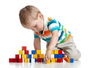 a little boy in a striped shirt building a wall with colorful square blocks