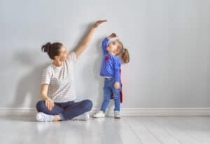 a mom measuring how tall her preschooler is getting