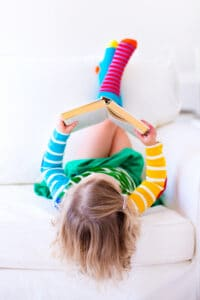 preschool girl reading upside down on the couch