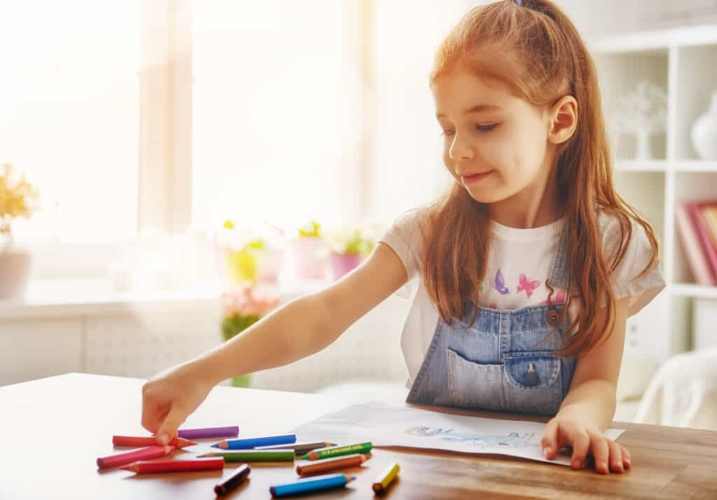 Preschool girl coloring in front of a window